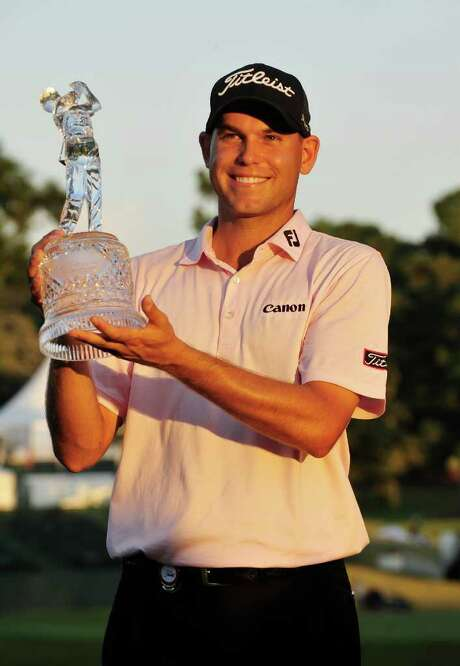 Bill Haas celebrates with the Tour Championship trophy after winning the Tour Championship golf tournament against Hunter Mahan after three playoff holes at East Lake Golf Club in Atlanta on Sunday, Sept. 25, 2011. (AP Photo/Rainier Ehrhardt) Photo: Rainier Ehrhardt / FR155191 AP