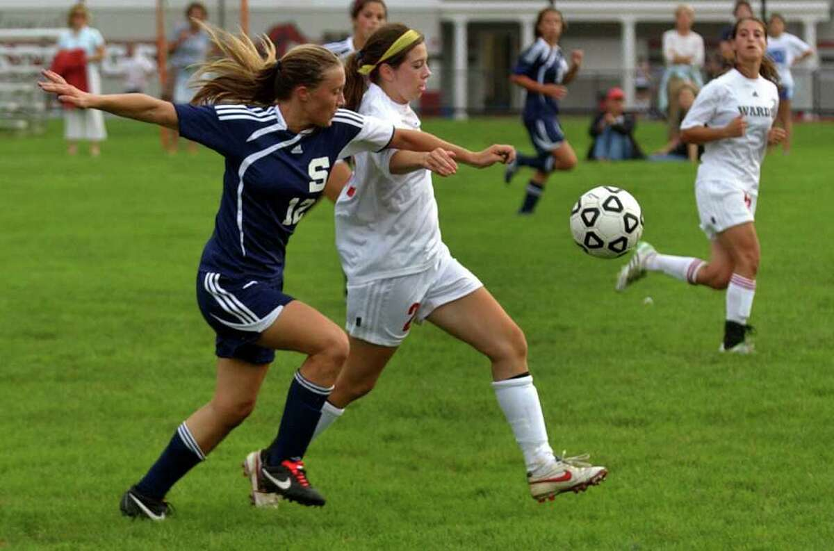 Staples' #12 Turner Block, left, and Fairfield Warde's #25 Megan Overby, chase down the ball during girls soccer action in Fairfield, Conn. on Tuesday September 27, 2011.