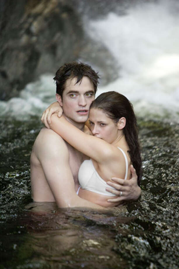 "My, how things heated up a few movies later. Here are Pattinson and Stewart as Edward and Bella in ""The Twilight Saga: Breaking Dawn Part 1."" (Getty Images) Photo: ANDRE COOPER / © 2011 Summit Entertainment, LLC. All Rights Reserved."