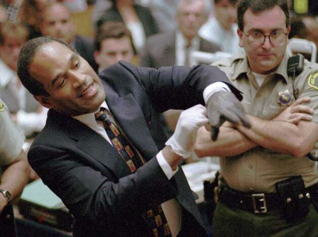 FILE--Murder defendant O.J. Simpson tries on one of the leather gloves prosecutors say he wore the night his ex-wife Nicole Brown Simpson and Ron Goldman were murdered, during the Simpson double-murder trial Thursday, June 15, 1995, in Los Angeles. From Fatty Arbuckle to O.J. Simpson, there have been so many trials of the century, this century. The one unfolding in the Senate against President Clinton is an improbable addition to a legacy shared by the famous, the powerless and now presidential. Photo: SAM MIRCOVICH, AP / REUTERS POOL