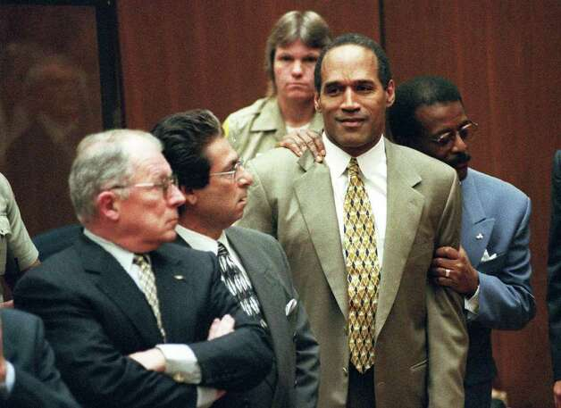 FILE--Attorney Johnnie Cochran Jr. holds onto O.J. Simpson as a not guilty verdict is read in a Los Angeles courtroom in this file photo taken Tuesday, Oct. 3, 1995.  Left is F. Lee Bailey and second from left is Robert Kardashian.  Nearly five years ago, the televised courtroom saga of Simpson gave Americans a chance to observe a justice system that long seemed remote.  It was perhaps an invaluable civics lesson, but one that will likely never happen again. Photo: MYUNG J CHUN, AP / DAILY NEWS POOL