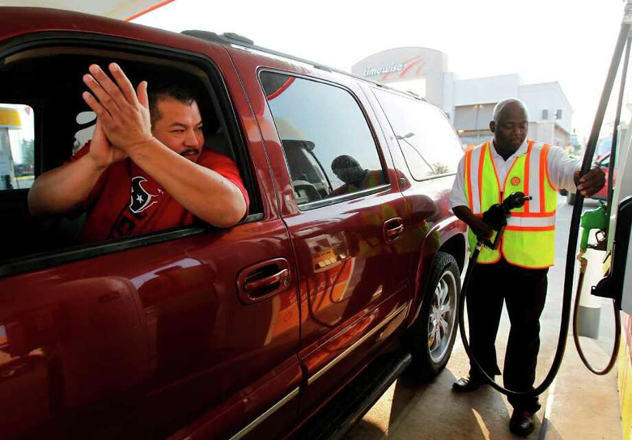 Jose Veloz claps from his Suburban as Sunny Ajose finishes pumping free gas for him at Timewise Shell station at 511 Lockwood, where Shell was giving away 15 gallons of free gas to customers, Wednesday, Sept. 28, 2011, in Houston. The event lasted from 7a.m. until 8:30a.m. in Houston, and was repeated in four cities nationwide. Photo: Karen Warren, Houston Chronicle / © 2011 Houston Chronicle