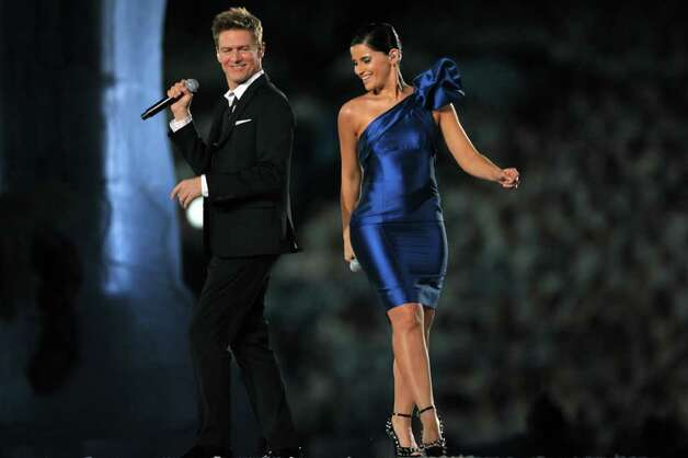 Canadian performers Bryan Adams (L) and Nelly Furtado sing during the opening ceremony for the Vancouver Winter Olympics at BC place in Vancouver on February 12, 2010.  The Games' build-up culminates with the lighting of the Olympic cauldron at BC Place in Vancouver, a ceremony held indoors for the first time in the competition's history.        AFP PHOTO / ADRIAN DENNIS Photo: ADRIAN DENNIS, AFP/Getty Images / 2010 AFP