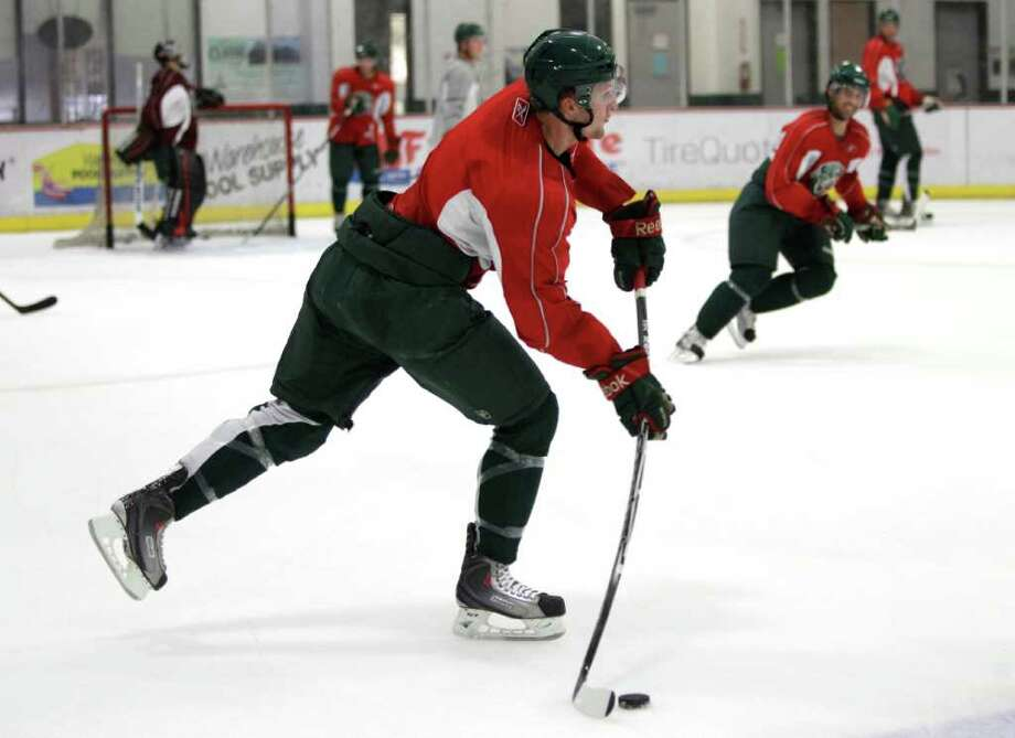Houston Aeros defenseman Kris Fredheim sends a puck up the ice during Aeros' hockey training camp at the Sugar Land Ice and Sports Center Wednesday, Sept. 28, 2011, in Sugar Land. Photo: Brett Coomer, Houston Chronicle / © 2011 Houston Chronicle