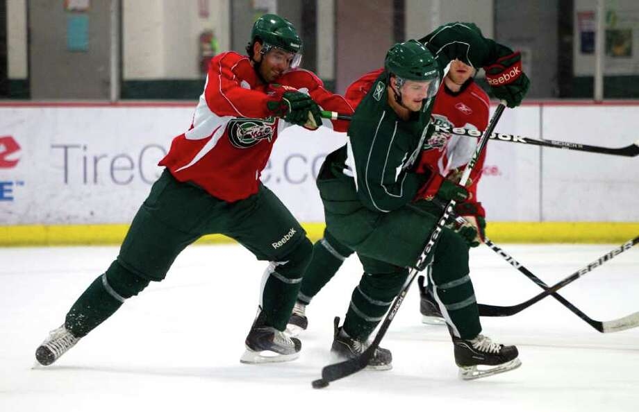 Houston Aeros defenseman Jamie Fritsch, left, and right wing Jarod Palmer battle for the puck during Aeros' hockey training camp at the Sugar Land Ice and Sports Center Wednesday, Sept. 28, 2011, in Sugar Land. Photo: Brett Coomer, Houston Chronicle / © 2011 Houston Chronicle