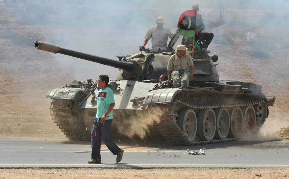 BELA SZANDELSZKY: ASSOCIATED PRESS LOOKING: Revolutionary fighters hitch a ride on a tank Wednesday while gathering on the main road outside Sirte, Libya, where one of Moammar Gadhafi's sons may be lurking. Photo: Bela Szandelszky / AP
