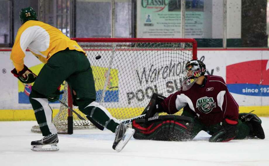 Houston Aeros defenseman Mike Hoffman (32) sends the puck past goalie Dennis Endras during Aeros' hockey training camp at the Sugar Land Ice and Sports Center Wednesday, Sept. 28, 2011, in Sugar Land. Photo: Brett Coomer, Houston Chronicle / © 2011 Houston Chronicle