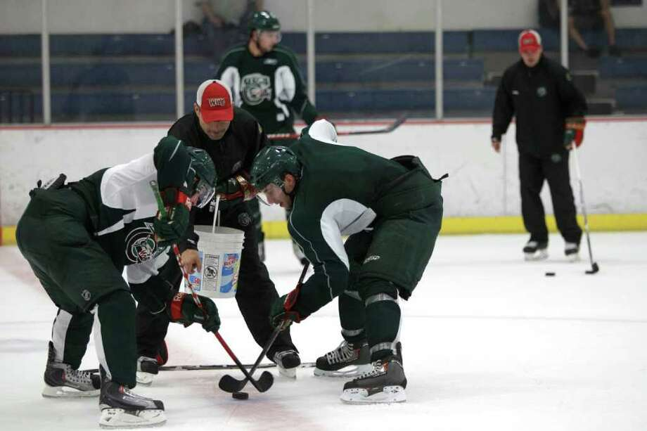 Houston Aeros assistant coach Sebastien Laplante, red hat, drops a puck during Aeros' hockey training camp at the Sugar Land Ice and Sports Center Wednesday, Sept. 28, 2011, in Sugar Land. Photo: Brett Coomer, Houston Chronicle / © 2011 Houston Chronicle