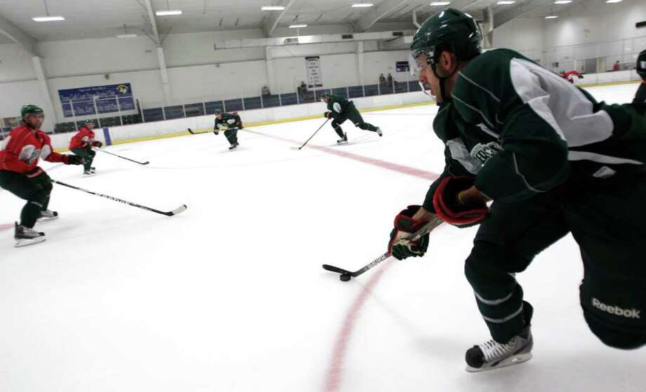 Houston Aeros forward J.P. Martignetti, right, controls the puck as he skates up the rink during Aeros' hockey training camp at the Sugar Land Ice and Sports Center Wednesday, Sept. 28, 2011, in Sugar Land. Photo: Brett Coomer, Houston Chronicle / © 2011 Houston Chronicle