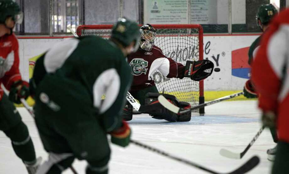 Houston Aeros goalie Dennis Endras reaches for a puck during Aeros' hockey training camp at the Sugar Land Ice and Sports Center Wednesday, Sept. 28, 2011, in Sugar Land. Photo: Brett Coomer, Houston Chronicle / © 2011 Houston Chronicle