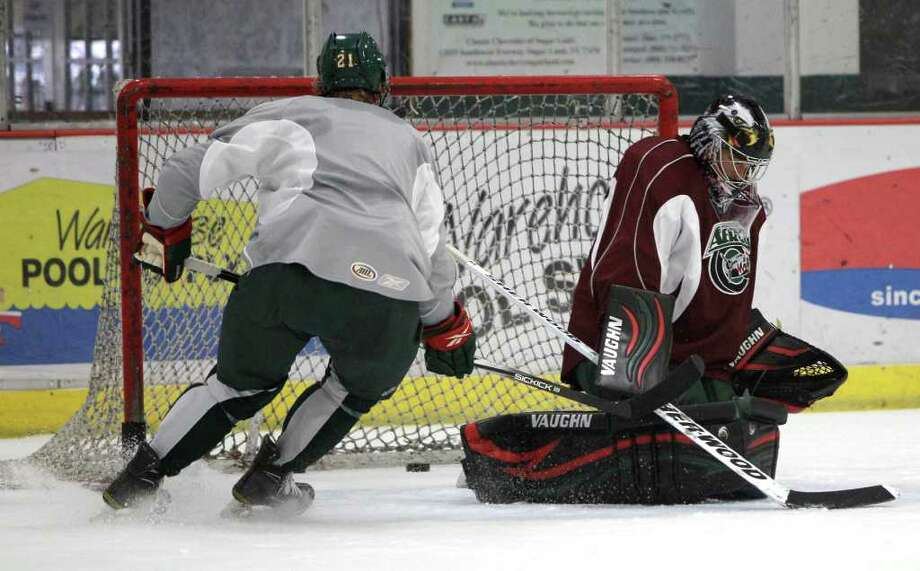 Houston Aeros right wing Mike Bartlett (21) takes a shot on goalie Dennis Endras, right, during Aeros' hockey training camp at the Sugar Land Ice and Sports Center Wednesday, Sept. 28, 2011, in Sugar Land. Photo: Brett Coomer, Houston Chronicle / © 2011 Houston Chronicle