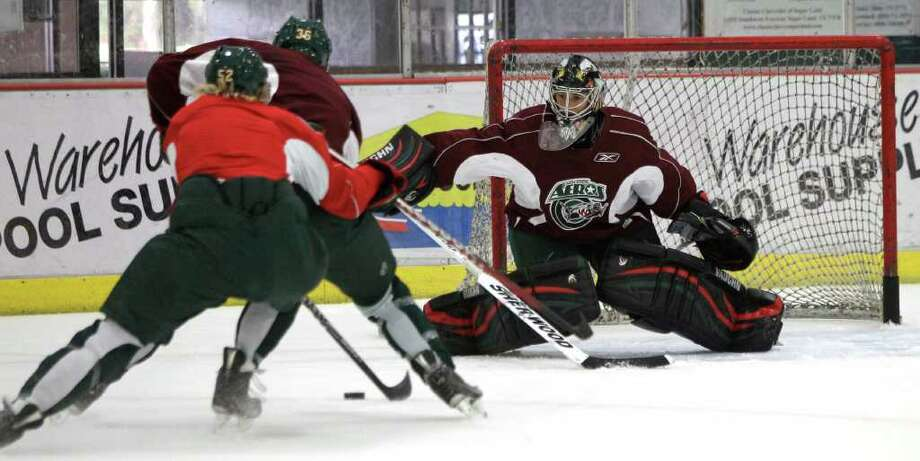 Houston Aeros Sam Lofquist (52) and Mike Dramer (36) take the puck toward goalie Dennis Endras during Aeros' hockey training camp at the Sugar Land Ice and Sports Center Wednesday, Sept. 28, 2011, in Sugar Land. Photo: Brett Coomer, Houston Chronicle / © 2011 Houston Chronicle