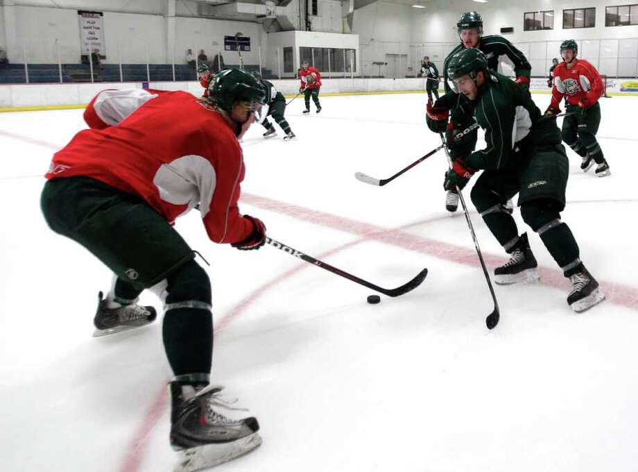 Houston Aeros Sam Lofquist, left, defends a drive with the puck by left wing Joel Broda during Aeros' hockey training camp at the Sugar Land Ice and Sports Center Wednesday, Sept. 28, 2011, in Sugar Land. Photo: Brett Coomer, Houston Chronicle / © 2011 Houston Chronicle