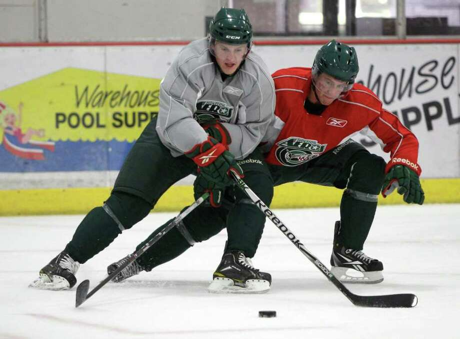 Houston Aeros right wing Mike Bartlett, left, and defenseman Chay Genoway battle for control of the puck during Aeros' hockey training camp at the Sugar Land Ice and Sports Center Wednesday, Sept. 28, 2011, in Sugar Land. Photo: Brett Coomer, Houston Chronicle / © 2011 Houston Chronicle