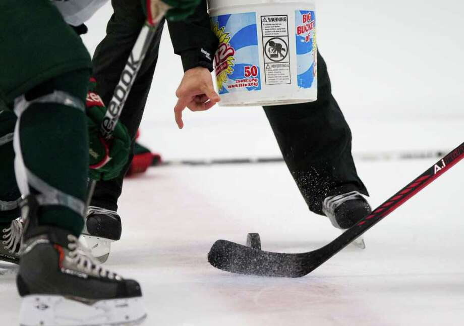 Houston Aeros assistant coach Sebastien Laplante drops a puck during Aeros' hockey training camp at the Sugar Land Ice and Sports Center Wednesday, Sept. 28, 2011, in Sugar Land. Photo: Brett Coomer, Houston Chronicle / © 2011 Houston Chronicle