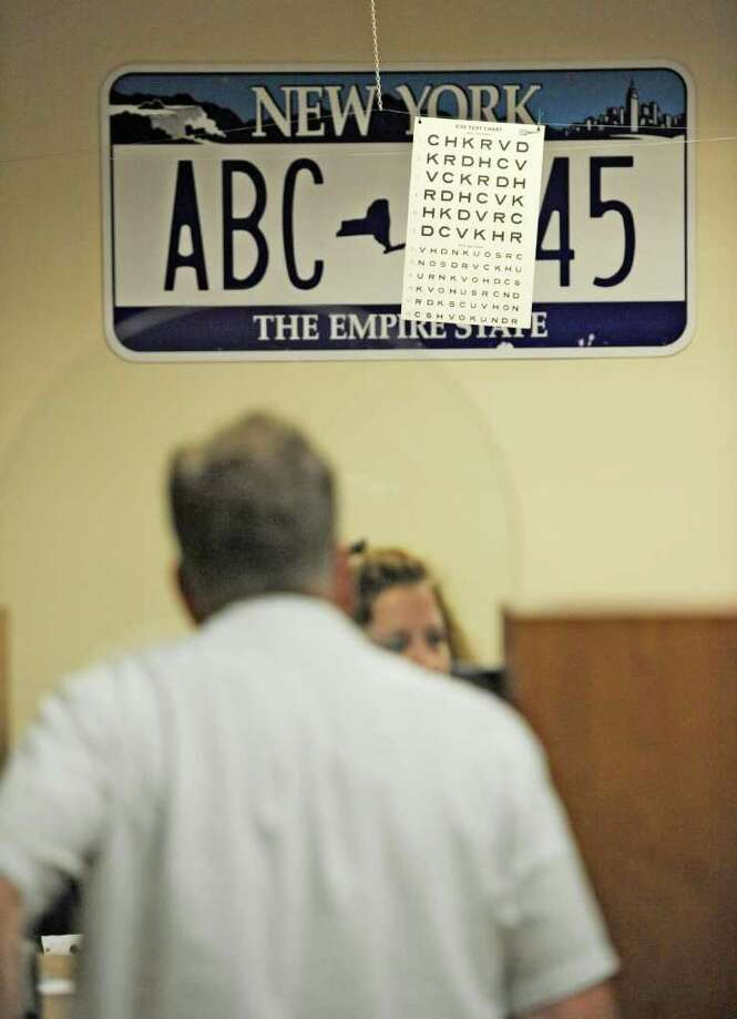 A person stands at the counter of the DMV in Troy, N.Y. September 28, 2011 while renewing his registration in the background is the eye test sign which will have very limited use from this day forward as a result of a rule change by the state government which will no longer require eye tests for renewal of licenses.   (Skip Dickstein / Times Union) Photo: SKIP DICKSTEIN / 00014797A