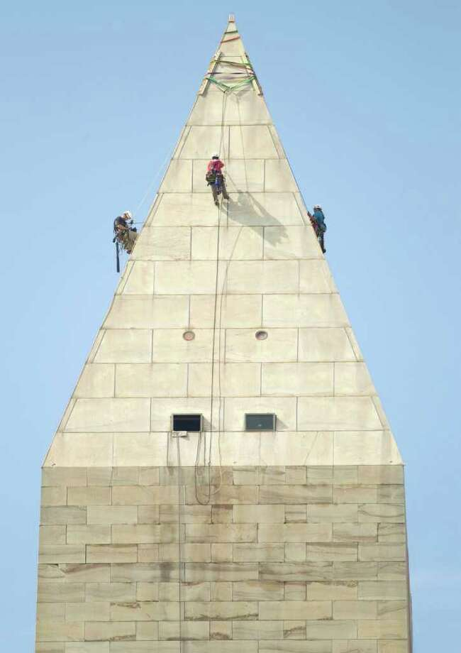 A team of engineers, from left, Dan Gach, Emma Cardini, center, and Katie Francis, harnessed to ropes , inspect the exterior of the Washington Monument for damage caused by last months earthquake, Wednesday, Sept. 28, 2011, in Washington.  (AP Photo/Evan Vucci) Photo: Evan Vucci