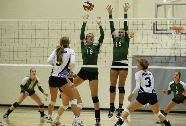 Reagan's Ashton Korona (16) and Brooke Sassin (15) attempt to make a block against Johnson in volleyball at Littleton Gym on Wednesday, Sept. 28, 2011. Johnson defeated Reagan in five games. Kin Man Hui/kmhui@express-news.net Photo: Kin Man Hui, -- / San Antonio Express-News