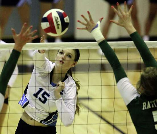 Johnson's Riley Caskey (15) hits between two Reagan blockers in volleyball at Littleton Gym on Wednesday, Sept. 28, 2011. Johnson defeated Reagan in five games. Kin Man Hui/kmhui@express-news.net Photo: Kin Man Hui, -- / San Antonio Express-News