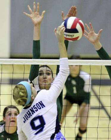Reagan's Ashlie Reasor (11) attempts to block a shot by Johnson's Katie Krietag (09) in volleyball at Littleton Gym on Wednesday, Sept. 28, 2011. Johnson defeated Reagan in five games. Kin Man Hui/kmhui@express-news.net Photo: Kin Man Hui, -- / San Antonio Express-News