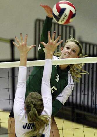 Reagan's Brooke Sassin (15) hits against Johnson's Jessica Teel (03) in volleyball at Littleton Gym on Wednesday, Sept. 28, 2011. Johnson defeated Reagan in five games. Kin Man Hui/kmhui@express-news.net Photo: Kin Man Hui, -- / San Antonio Express-News