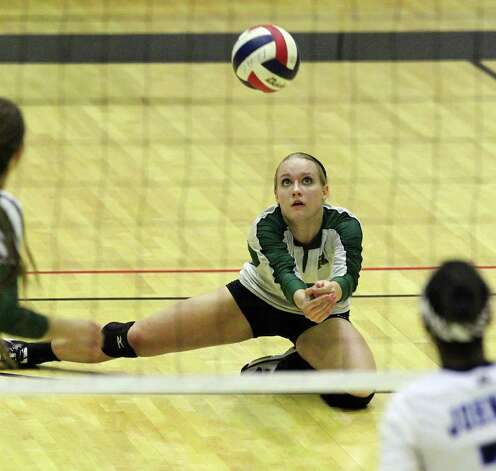 Reagan's Katie Medell (03) gets low for a return against Johnson in volleyball at Littleton Gym on Wednesday, Sept. 28, 2011. Johnson defeated Reagan in five games. Kin Man Hui/kmhui@express-news.net Photo: Kin Man Hui, -- / San Antonio Express-News