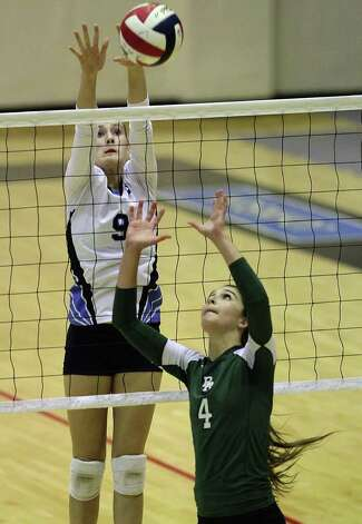 Johnson's Kassie Frietag (09) stretches for a block against Reagan's Morgan Reed (04) in volleyball at Littleton Gym on Wednesday, Sept. 28, 2011. Johnson defeated Reagan in five games. Kin Man Hui/kmhui@express-news.net Photo: Kin Man Hui, -- / San Antonio Express-News