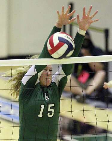 Reagan's Brooke Sassin (15) makes a block against Johnson in volleyball at Littleton Gym on Wednesday, Sept. 28, 2011. Johnson defeated Reagan in five games. Kin Man Hui/kmhui@express-news.net Photo: Kin Man Hui, -- / San Antonio Express-News