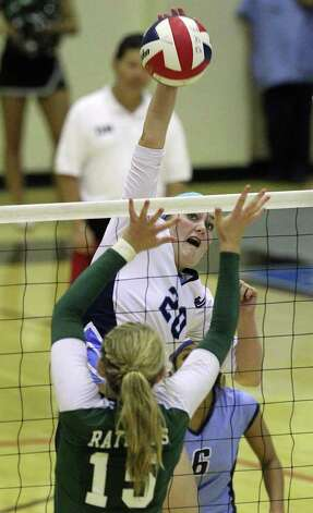 Johnson's Olivia Drummond (20) hits over Reagan's Brooke Sassin (15) in volleyball at Littleton Gym on Wednesday, Sept. 28, 2011. Johnson defeated Reagan in five games. Kin Man Hui/kmhui@express-news.net Photo: Kin Man Hui, -- / San Antonio Express-News
