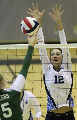 Johnson's Sarah Wilson (12) reaches to attempt a block against Reagan's Brooke Sassin (15) in volleyball at Littleton Gym on Wednesday, Sept. 28, 2011. Johnson defeated Reagan in five games. Kin Man Hui/kmhui@express-news.net Photo: Kin Man Hui, -- / San Antonio Express-News