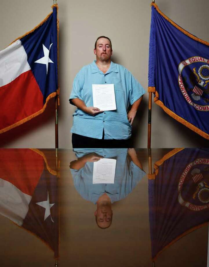Ronald Kratz II holds a copy of the lawsuit he filed against BAE Systems. Photo: File Photo / Houston Chronicle