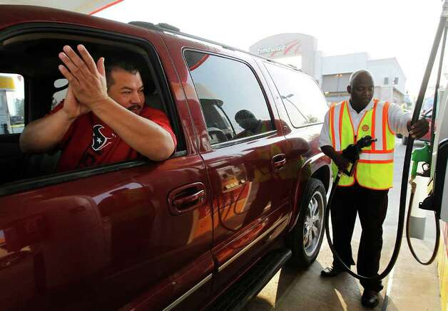 Jose Veloz claps as Timewise employee Sunny Ajose finishes pumping free gas for Veloz's SUV in Houston on Wednesday. For 90 minutes, Shell gave away 15 gallons of gas to customers. Company spokesman Sergio Roldan said the giveaway was designed to showcase the benefits of high-quality gas. The event also was held in four other cities across the country. Photo: Karen Warren/Houston Chronicle / © 2011 Houston Chronicle