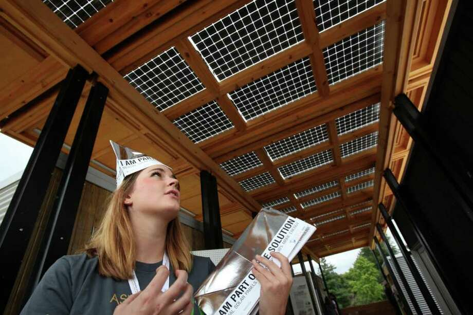 Jacqueline Stewart of Appalachian State University explains the importance of bifacial solar panels, top, on The Solar Homestead while distributing foldable hats that double as a brochure, at the U.S. Department of Energy Solar Decathlon in Washington, D.C., Wednesday, Sept. 21, 2011.  The panels collect power on both sides, from direct and reflected light, while providing filtered daylight and protection from the elements. Photo: Stefano Paltera, Stefano Paltera/U.S. Department Of Energy Solar Decathlon / Copyright Notice: © 2011 Stefano Paltera/U.S. Department of Energy Solar Decathlon