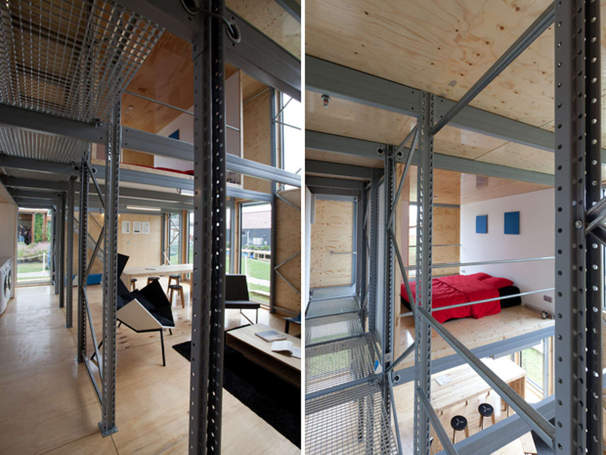 The interior of E-Cube, by Team Belgium, is pictured at the U.S. Department of Energy Solar Decathlon 2011 in Washington, D.C. The building is envisioned as an affordable kit that can be assembled in days, thanks to such approaches as: A façade made of fiber-cement boards with the same dimensions as the triple-glazed window elements; An interior stripped of most conventional finishes, saving on materials and easing construction; A standard pallet rack system that creates the main structure using a bolt-less assembly process; A plug-and-play electrical wiring system that is integrated into the structure for easy installation; A floor plan that can be expanded by adding more floor panels on the existing beams.