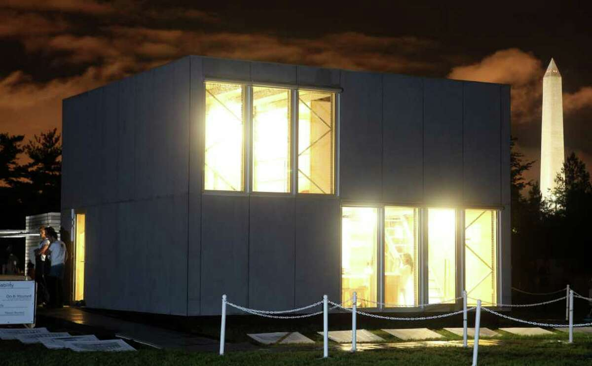 The exterior of E-Cube, by Team Belgium, is pictured at night on Sept. 23, 2011 at the U.S. Department of Energy Solar Decathlon 2011 in Washington, D.C. The building is envisioned as an affordable kit that can be assembled in days, thanks to such approaches as: A façade made of fiber-cement boards with the same dimensions as the triple-glazed window elements; An interior stripped of most conventional finishes, saving on materials and easing construction; A standard pallet rack system that creates the main structure using a bolt-less assembly process; A plug-and-play electrical wiring system that is integrated into the structure for easy installation; A floor plan that can be expanded by adding more floor panels on the existing beams.