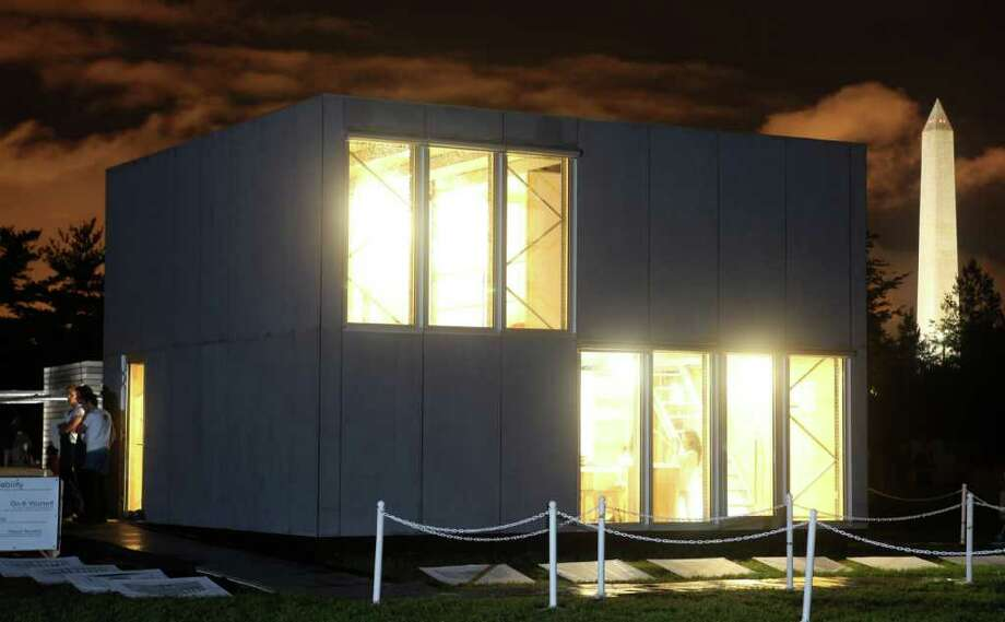 The exterior of E-Cube, by Team Belgium, is pictured at night on Sept. 23, 2011 at the U.S. Department of Energy Solar Decathlon 2011 in Washington, D.C. The building is envisioned as an affordable kit that can be assembled in days, thanks to such approaches as: A façade made of fiber-cement boards with the same dimensions as the triple-glazed window elements; An interior stripped of most conventional finishes, saving on materials and easing construction; A standard pallet rack system that creates the main structure using a bolt-less assembly process; A plug-and-play electrical wiring system that is integrated into the structure for easy installation; A floor plan that can be expanded by adding more floor panels on the existing beams. Photo: Stefano Paltera, Stefano Paltera/U.S. Department Of Energy Solar Decathlon / Copyright Notice: © 2011 Stefano Paltera/U.S. Department of Energy Solar Decathlon