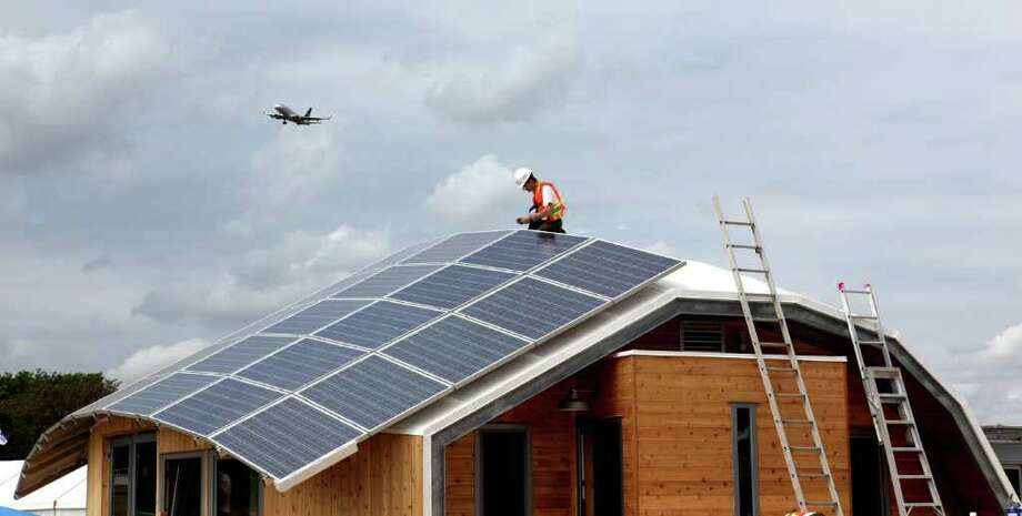 A student from works on the solar panels atop TRTL (Technological Residence, Traditional Living), by the University of Calgary, on Sept. 19, 2011 at the U.S. Department of Energy Solar Decathlon 2011, in Washington, D.C. The house is inspired by native tepees and designed to provide housing for Canadian First Nations people. Features include: