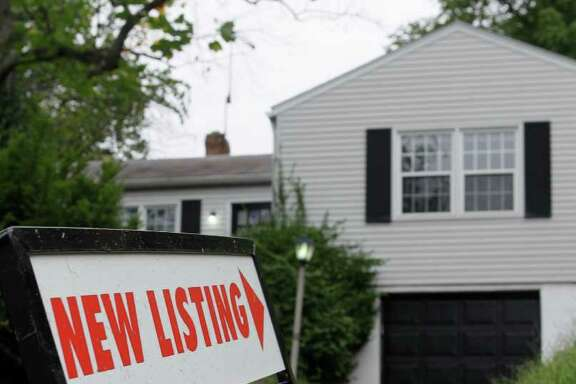 In this photo taken Sept. 27, 2011, a real estate sign is posted outside a newly listed home for sale, in Cincinnati.  Fixed mortgage rates have fallen to historic new lows for a fourth straight week and are likely to fall further. Freddie Mac says the average on a 30-year fixed mortgage fell to 4.01 percent this week. That's the lowest rate since 1951. (AP Photo/Al Behrman)