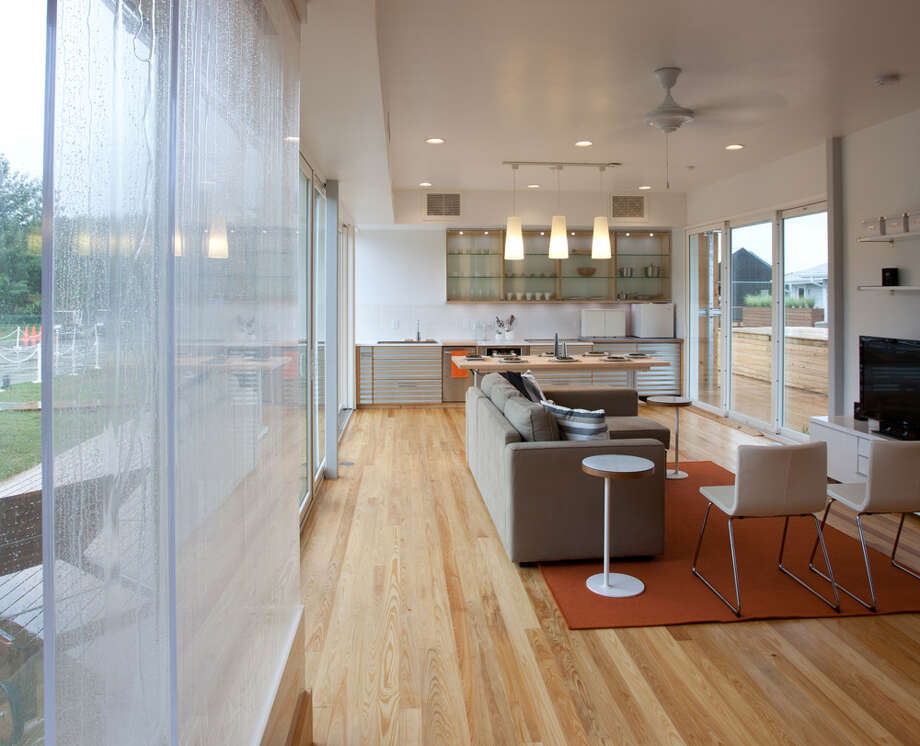 The interior of FLeX House, by Team Florida (The University of South Florida, Florida State University, The University of Central Florida and The University of Florida) is seen at the U.S. Department of Energy Solar Decathlon 2011, in Washington, D.C. The House base module is designed for a young couple, possibly with a small child. New modules can be added as the family grows. Other features include: A compact design that can be shipped on one truck and quickly deployed at a building site; Cypress louvers that shield the roof and walls from the hot Florida sun; A wall that opens to allow cool air in during mild months; Corrugated metal siding that reflects sunlight and is durable and economical; Landscaping that treats stormwater runoff, provides food and moderates temperatures; A liquid desiccant duct system that connects to an energy recovery ventilator to dehumidify incoming air. Photo: Jim Tetro/U.S. Department Of Energy Solar Decathlon
