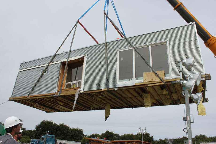 Team Florida (The University of South Florida, Florida State University, The University of Central Florida and The University of Florida)  lowers a module of FLeX House at the U.S. Department of Energy Solar Decathlon 2011, in Washington, D.C. The House base module is designed for a young couple, possibly with a small child. New modules can be added as the family grows. Other features include: