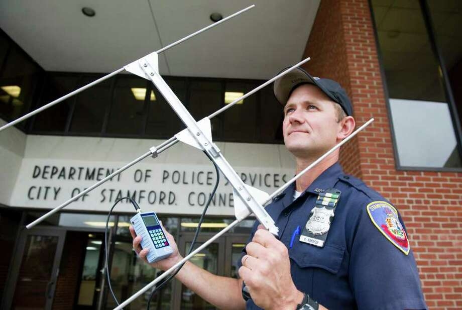 Stamford police officer Greg Rokoczy holds a Project Lifesaver transmitter at police headquarters in Stamford Conn., Sept. 29, 2011.  Project Lifesaver is a national program that outfits Alzheimer's patients with a bracelet equipped with a radio transmitter allowing law enforcement to track their whereabouts if they go missing. This past weekend Rakoczy helped make the first rescue in the state using the Project Lifesaver when he tracked down a 80-year-old man who left home and wandered through downtown Stamford. Photo: Keelin Daly / Stamford Advocate