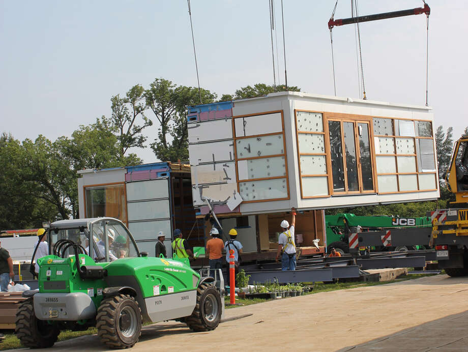 """Sections of Solar Roofpod, by Team New York (The City College of New York), are craned into place at  the U.S. Department of Energy Solar Decathlon 2011, in Washington, D.C. The home is intended to go on the roofs of existing mid-rise buildings and features: 64 poplar wood-framed """"building blocks"""" that can be custom fitted with glazed, opaque, louvered or screened cladding, based on such variables as solar orientation, predominant wind direction, preferred view and interior layout; A rooftop-mounted solar trellis that protects the house from heat gain and is easy to upgrade with new solar-power technologies; A radiant floor system that uses solar heat. Photo: Stefano Paltera/U.S. Department Of Energy Solar Decathlon"""