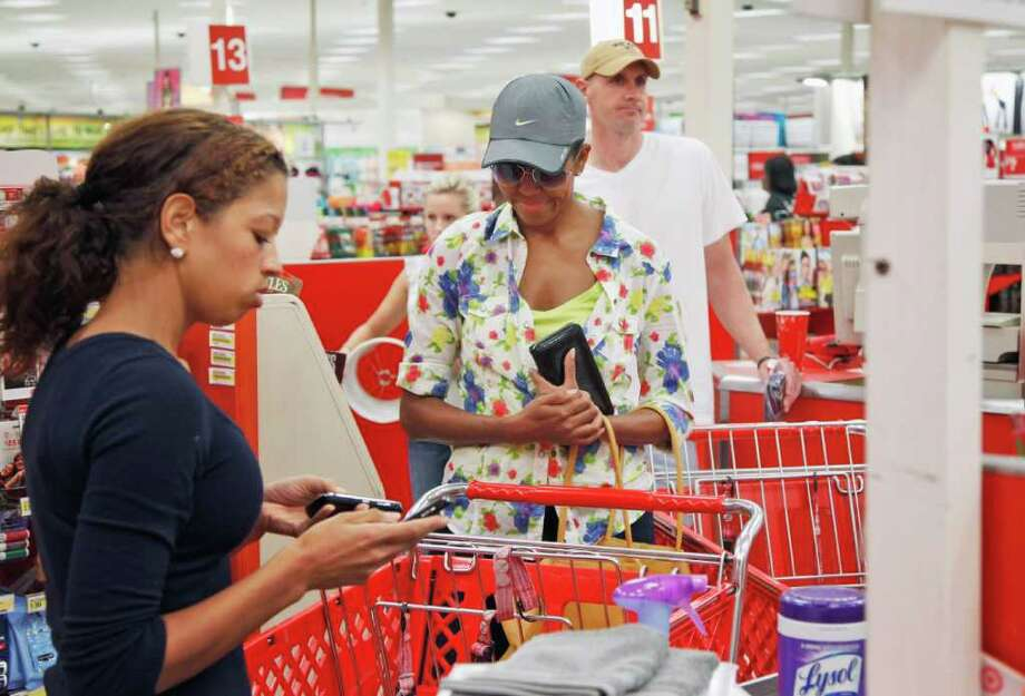 First lady Michelle Obama, wearing a hat and sunglasses, center, stands in line at a Target Department store in Alexandria, Va., Thursday, Sept. 29, 2011, after doing some shopping. (AP Photo/Charles Dharapak) Photo: Charles Dharapak / AP