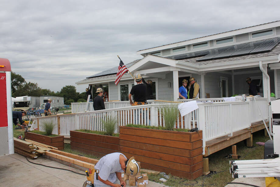 Purdue students work on INhome at the U.S. Department of Energy Solar Decathlon 2011, in Washington, D.C. The exterior is designed to blends in to a typical Midwestern neighborhood. Photo: Stefano Paltera/U.S. Department Of Energy Solar Decathlon