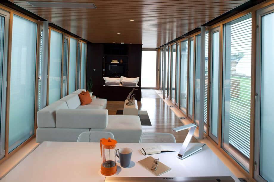 The interior of Living Light, by the University of Tennessee, is seen at the U.S. Department of Energy Solar Decathlon 2011, in Washington, D.C. The house features: A design inspired by the cantilever barns of southern Appalachia; A dynamic double facade system made of alternating translucent and transparent panes of glass, with horizontal blinds between the panes; An energy recovery ventilator that harvests air through the double facade system to supply the house with passively warmed or cooled fresh air; Sensors that automatically manage the electric lighting, including color-changing LED strip lights along the facade; A home automation system that can be programmed with preferred conditions for activities, such as watching a movie or entertaining dinner guests; Cylindrical solar modules that capture sunlight across their entire surface. Photo: Jim Tetro/U.S. Department Of Energy Solar Decathlon