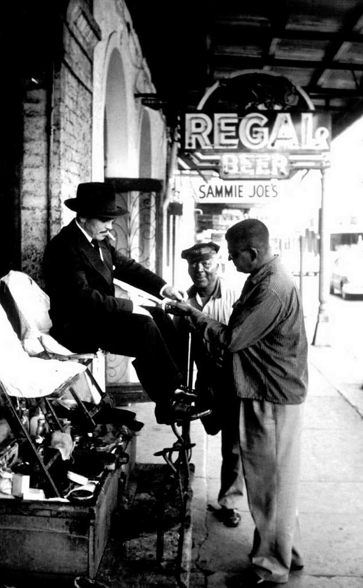 John Howard Griffin, right, collects money from a patron at a shoeshine stand belonging to Sterling Williams, center, where he worked for a few days in November 1959. (Appears in Griffin's book, Black Like Me)