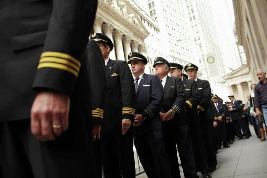 Spencer Platt : Getty Images OPPOSED: Continental and United pilots demonstrate on Wall Street over the lack of progress on a union accord. Photo: Spencer Platt / 2011 Getty Images
