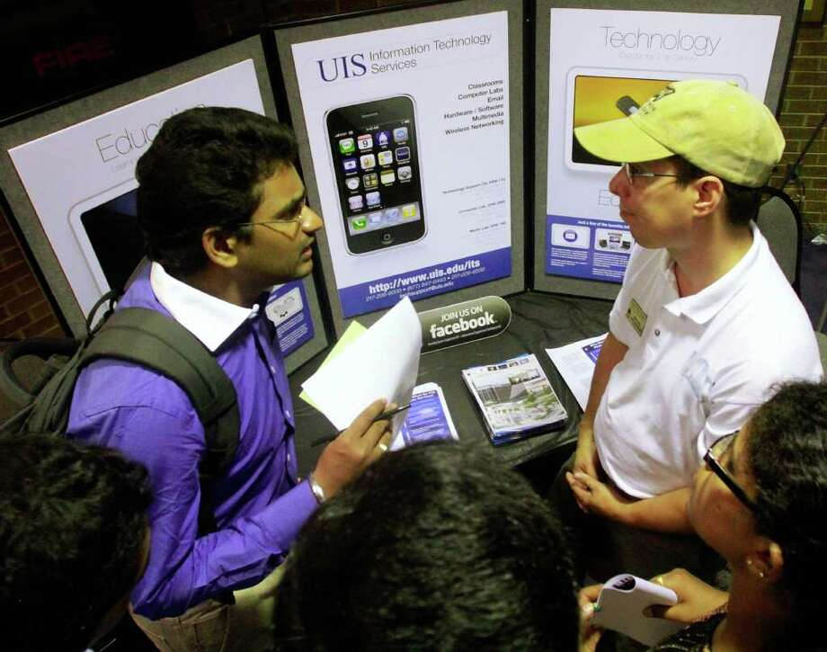 SETH PERLMAN : ASSOCIATED PRESS JOB FAIR: Recruiter Krish Kilaru, left, talks with candidates at a job fair in Springfield, Ill., this month. The number seeking unemployment benefits fell to the lowest level in five months. Photo: Seth Perlman / AP