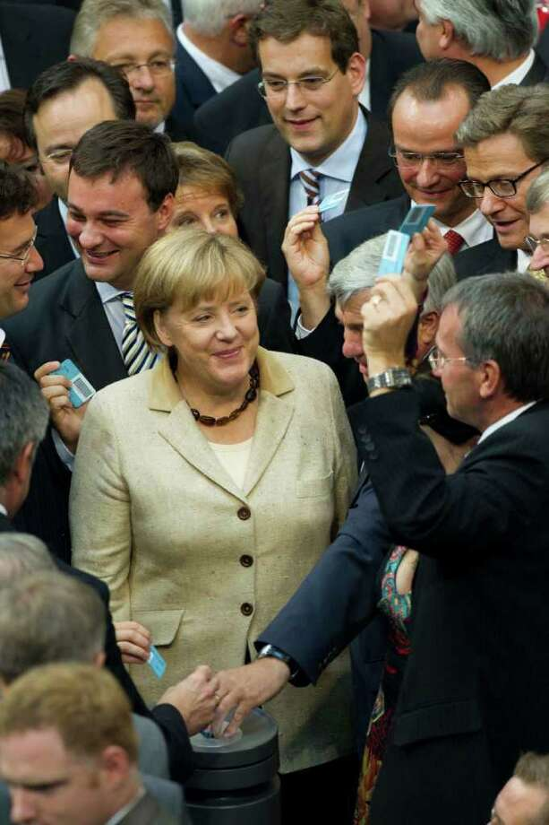German Chancellor Angela Merkel reacts after she casts her vote about the eurozone bailout fund at the German parliament Bundestag in Berlin, Thursday, Sept. 29, 2011. German lawmakers are expected to approve new powers Thursday for the eurozone bailout fund in a major step toward tackling the bloc's sprawling sovereign debt crisis.  (AP Photo/Markus Schreiber) Photo: Markus Schreiber / AP