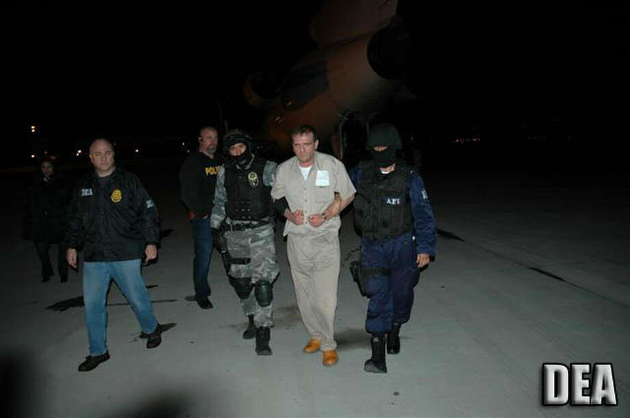 """Hector """"El Guero"""" Palma Salazar, a former head of the Sinaloa Cartel, is set to be released from prison Saturday, June 11, 2016, according to the U.S. Bureau of Prisons.In this photo, Palma is escorted by U.S. and Mexican federal agents after landing in Houston in January 2007 to face federal charges in the United States.He is expected to return to the Sinaloa Cartel. / DirectToArchive"""